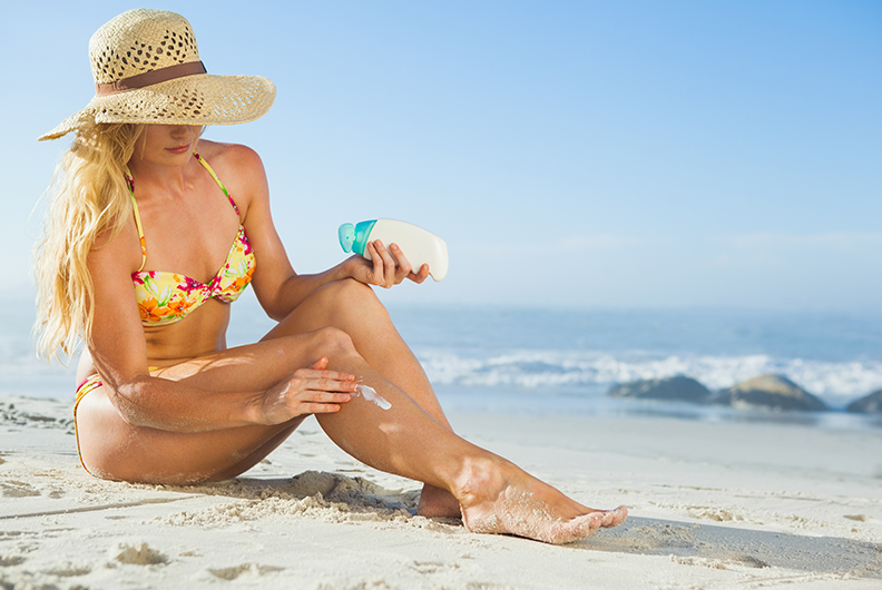 imagem de uma mulher branca, de cabelo loiro, na praia. Ela está sentada na areia, com as pernas levemente curvadas, enquanto passa filtro solar na perna direita. A mulher está usando um biquini amarelo com flores e um chapéu de palha.