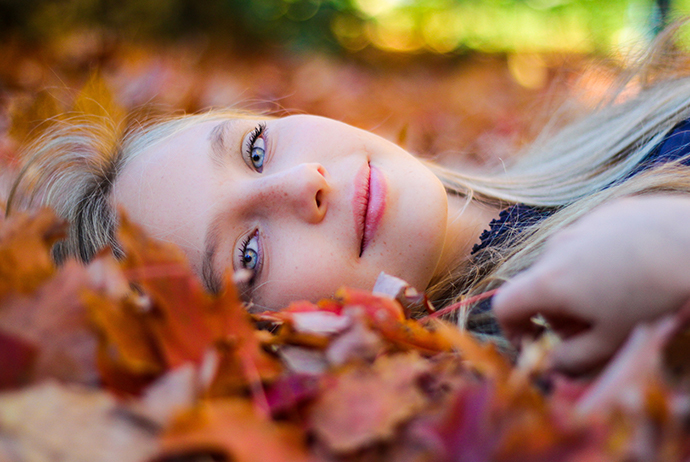 Uma mulher branca, com cabelos loiros e olhos azuis está no centro da imagem. Ela está deitada sobre folhas secas, olha para a frente e sorri. Ela veste uma blusa azul.