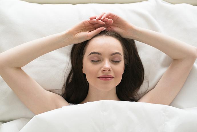 uma mulher branca, de longos cabelos escuros, está deitada de costas em uma cama, com o semblante relaxado e olhos fechados. Ela está com os braços levantados e as mãos posicionadas no topo da cabeça. Seu travesseiro e edredom são brancos.