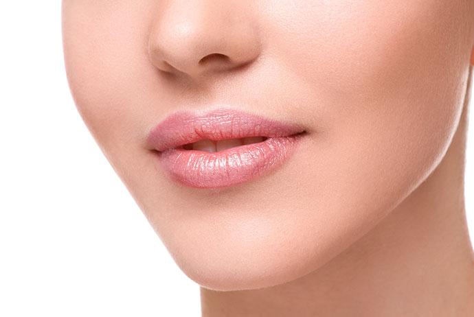 Em close, a imagem exibe a região inferior da face de uma mulher. Ela é branca, usa batom rosa-claro e está com os lábios entreabertos. Sua cabeça está voltada para a esquerda, e o fundo da imagem é branco.